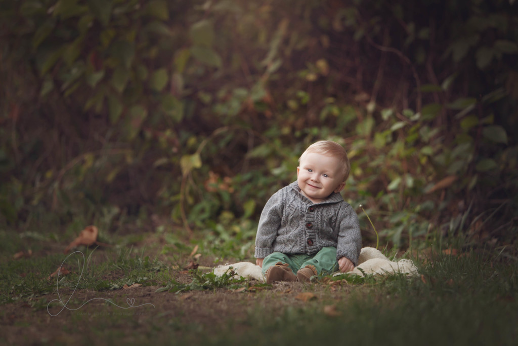 smiling baby boy sitting up outdoors